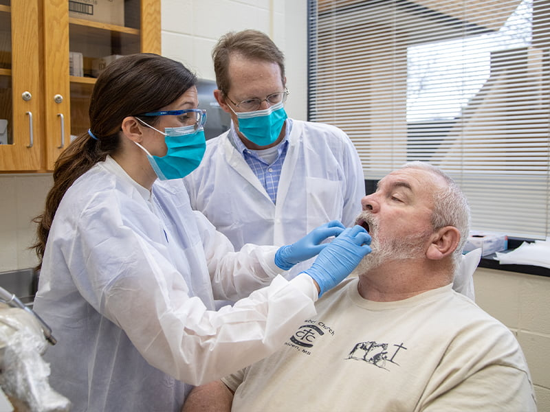 Two dentists check a patients mouth.