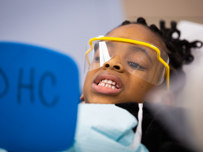 Girl in yellow dental glasses looks at her teeth in mirror.