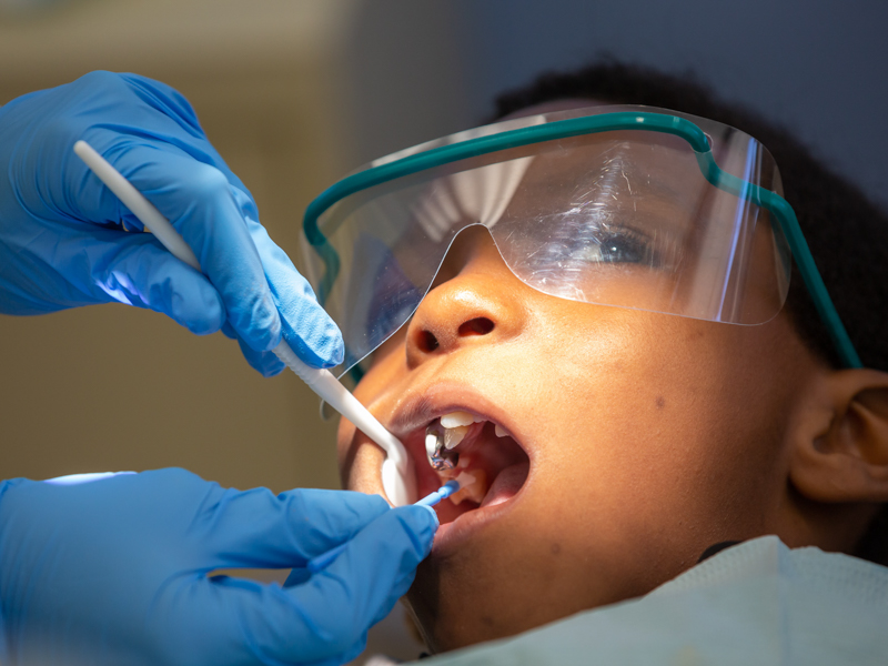 Close of up patient with dental tools in mouth.