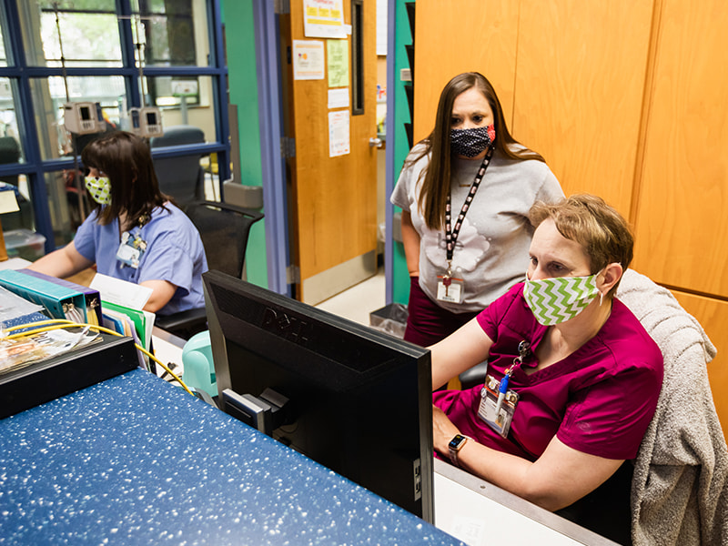 Wearing masks while working to prevent the spread of COVID-19 are, from left, Hannah Alfonso, nurse; Jennifer Smith, social worker; and Tammy Roberts, nurse.