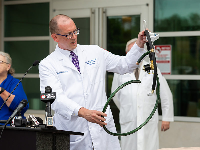Dr. Charles Robertson, assistant professor of anesthesiology, holds up a ventilator built from garden hose and other readily available parts. The ventilators are meant for use only if UMMC exhausts other ventilator options.