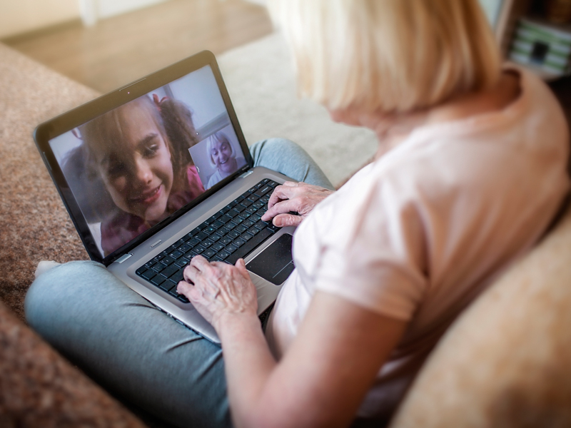 girl talking with her grandmother within video chat on laptop