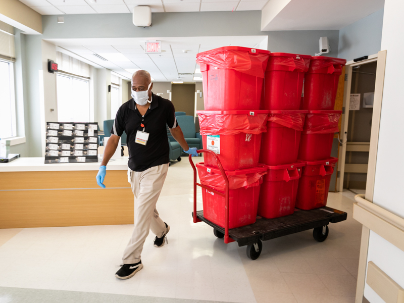 Housekeeper Bill Culpepper pulls a dolly laden with nine hazardous waste containers holding soiled and contaminated personal protective equipment and medical supplies from the medical ICU.