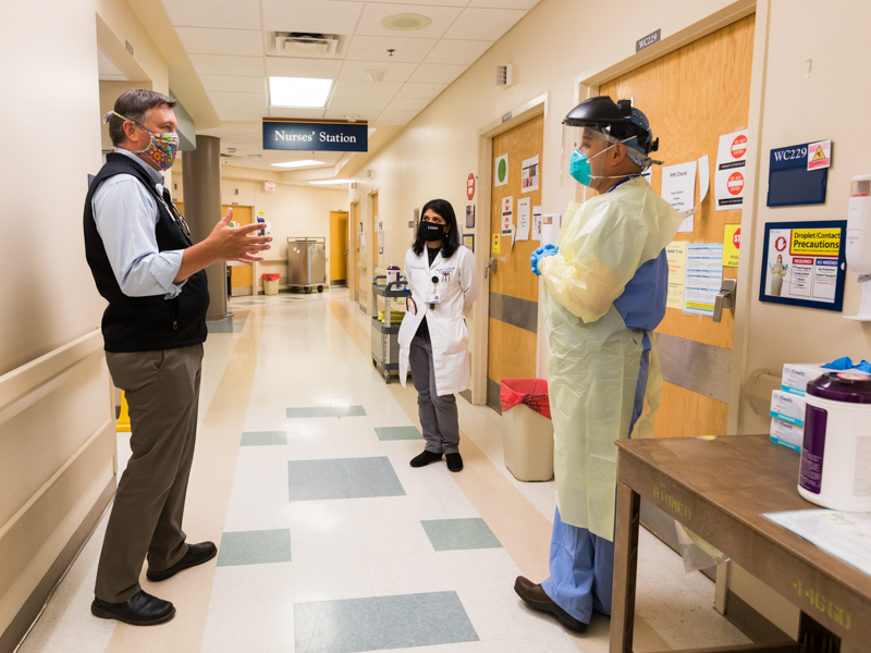 Dr. Jason Parham, left, and Dr. Bhagyashri Navalkele, center, confer with Dr. Luis Shimose Ciudad, an infectious diseases and critical care physician, before he enters a COVID-19 patient room on 2 North.