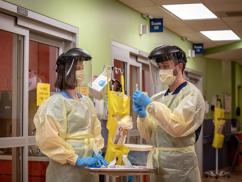 Anne Sinclair, a nurse in the pediatric emergency department, shows Oxford accelerated nursing student Logan Christian, right, how to apply proper PPE and how to perform a COVID-19 swab.