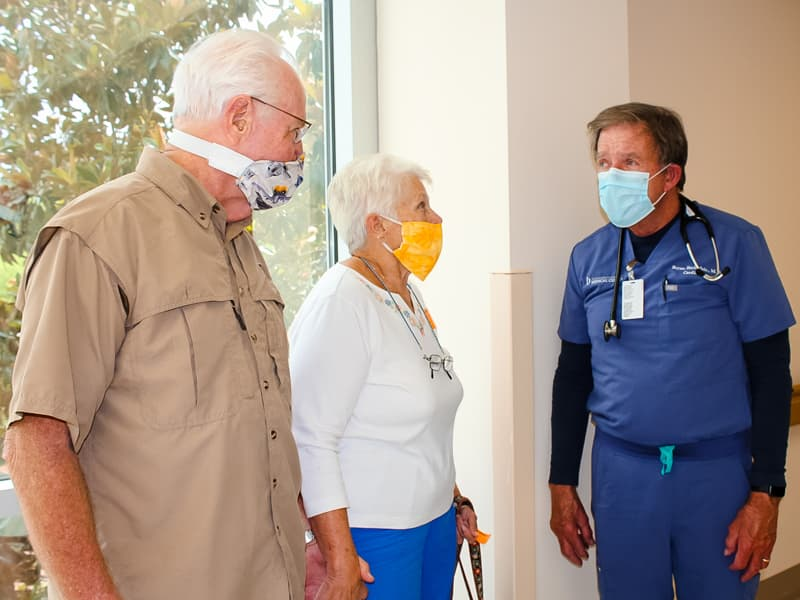University of Mississippi Medical Center cardiologist Dr. Bryan Barksdale, right, chats with patient John Orton and Orton's wife, Linda.