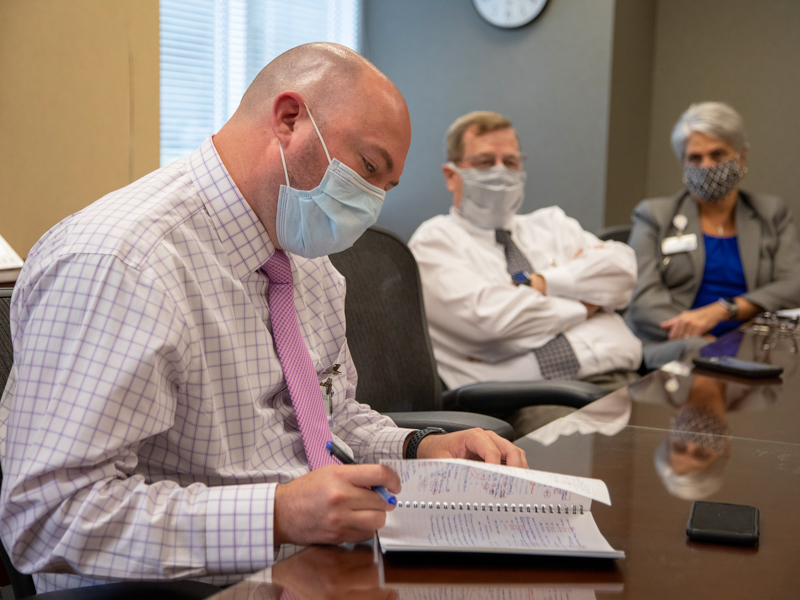 Jason Zimmerman, left, associate chief nursing officer for adult nursing services, reviews notes during the UMMC Health System weekly leadership meeting to discuss COVID-19 response.