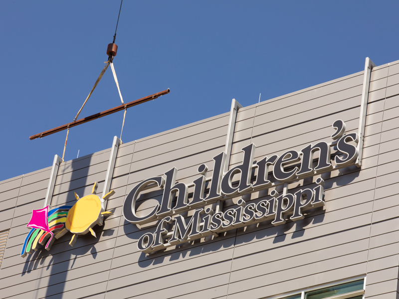 The Children's of Mississippi sign is shown being placed on the Kathy and Joe Sanderson Tower.
