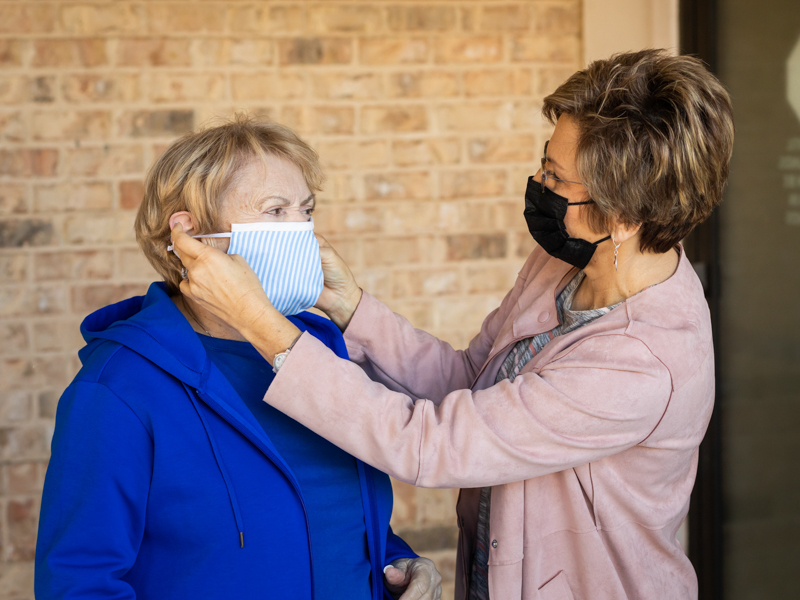 Darlene Bryant, right, helps her mother, Bonnie Acey, with her mask during a recent visit at an assisted living facility.