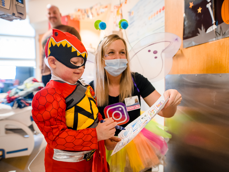 Children's of Mississippi patient Cash Ward of Summit plays a costume scavenger hunt game with child life specialist Tiffany Key, who is dressed as a social (media) butterfly.