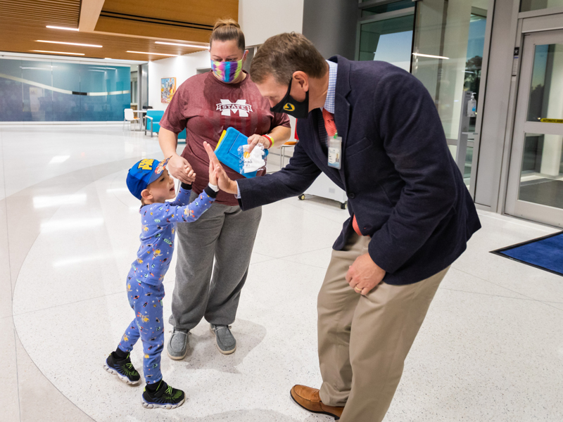 After hand-sanitizing, Guy Giesecke, Children's of Mississippi CEO, and Jovi McCloud of Morton, the first patient to enter the Kathy and Joe Sanderson Tower at Children's of Mississippi, share a high-five as Jovi's mother, Amy McCloud, watches with approval.