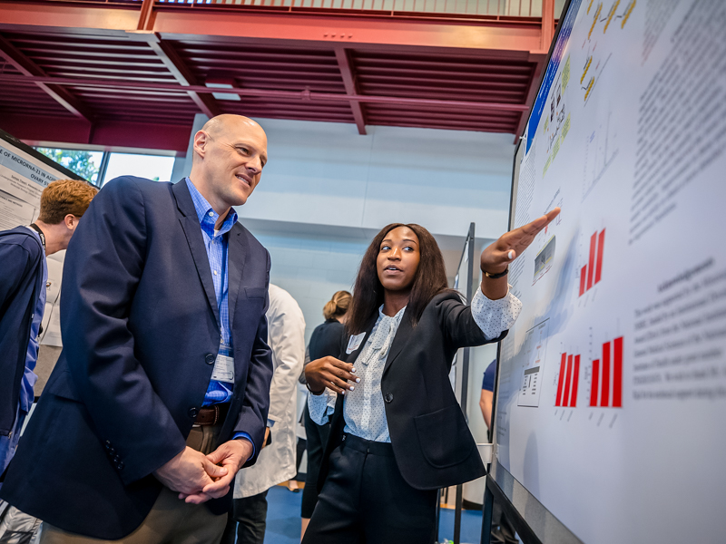 "Kristen Smith, a Summer Undergraduate Research Experience student, explains her project to Dr. Michael Ryan during the SURE Symposium in summer 2019. SURE is a pipeline training program that is part of the Mississippi Diversity in Hypertension and Cardiorenal Research Program, which was recently awarded a ""Perfect 10"" score by a National Institutes of Health review committee."