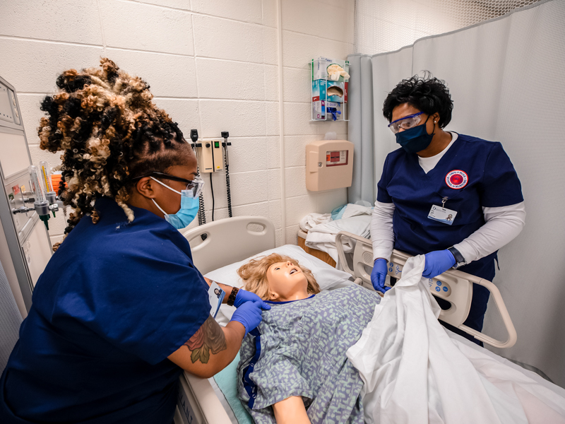 During their first week in the Accelerated BSN program, Asia Madison, left, and Erica Logan practice tucking a mannequin