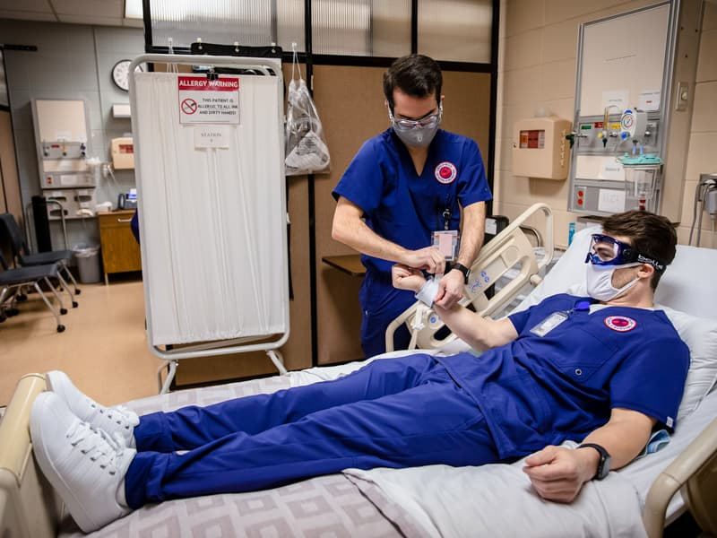 Blake McClure and Austin Oalmann practice skills in an Accelerated BSN nursing simulation lab.