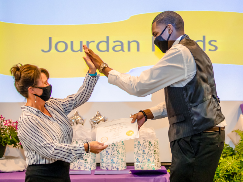 Project SEARCH Instructor Christina Guarino and graduate Jourdan Hinds high five during the Project SEARCH graduation ceremony May 14.