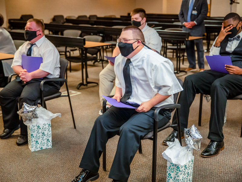Graduates laugh while watching a slideshow during the Project SEARCH graduation ceremony