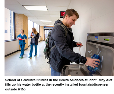 School of Graduate Studies in the Health Sciences student Riley Alef fills up his water bottle at the recently installed fountain/dispenser outside R153.