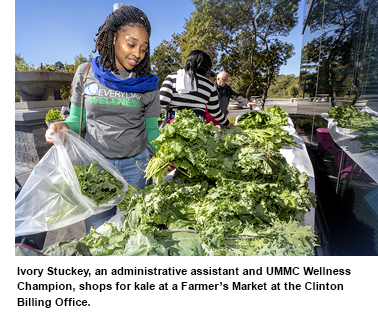 Ivory Stuckey, an administrative assistant and UMMC Wellness Champion, shops for kale at a Farmer's Market at the Clinton Billing Office.