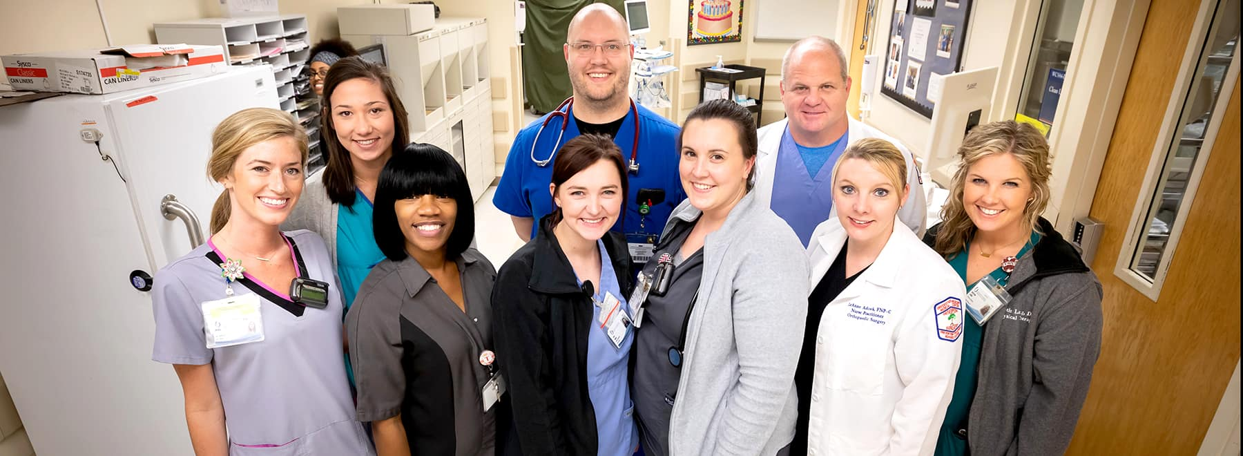 Group of male and female UMMC medical staff from the orthopedics departments pose in front of a nurses'  station.