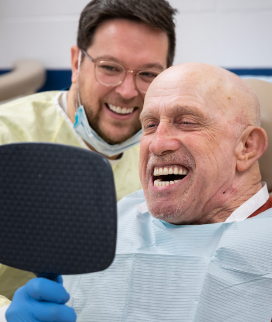 Man smiles while looking at his new dentures as student looks over his shoulder