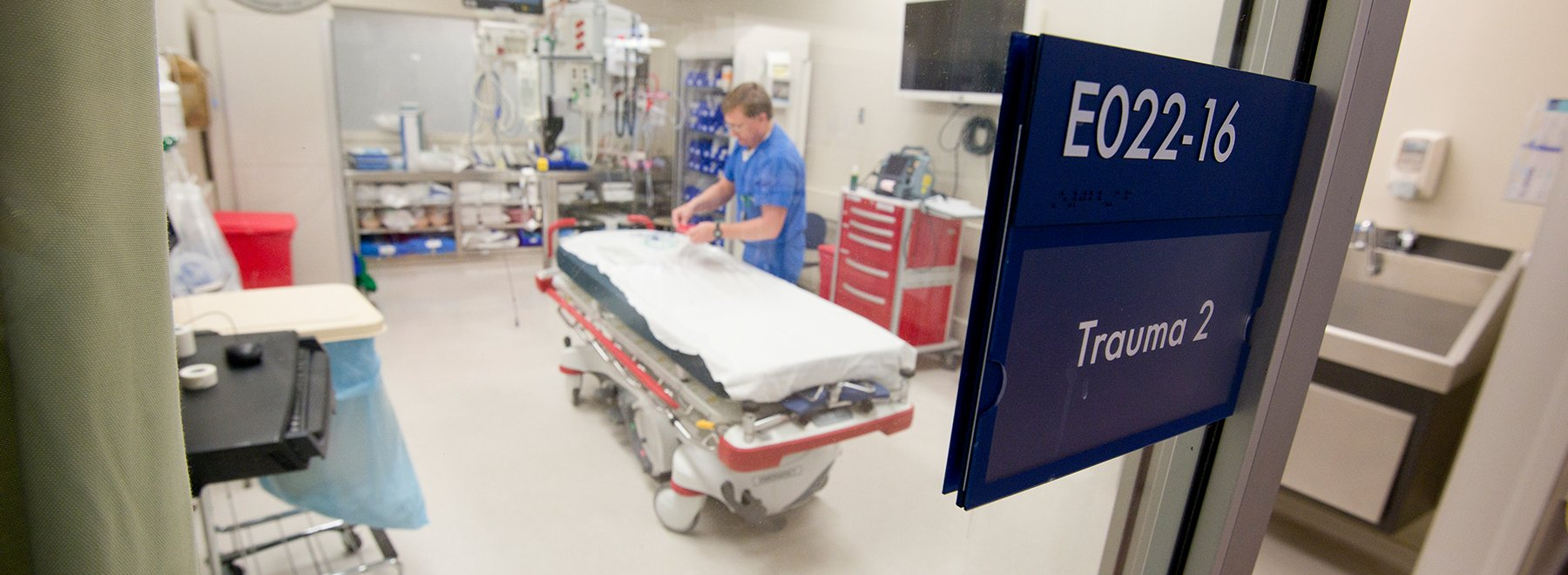 Male staff member readying a hospital bed in an empty trauma room