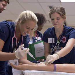 Students work with IV arms during simulation.