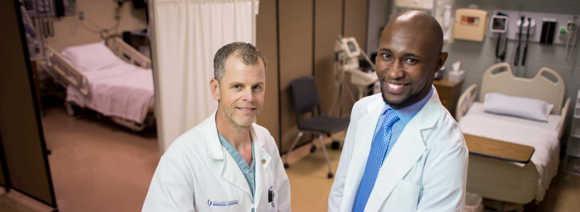 Two men standing in a clinical setting